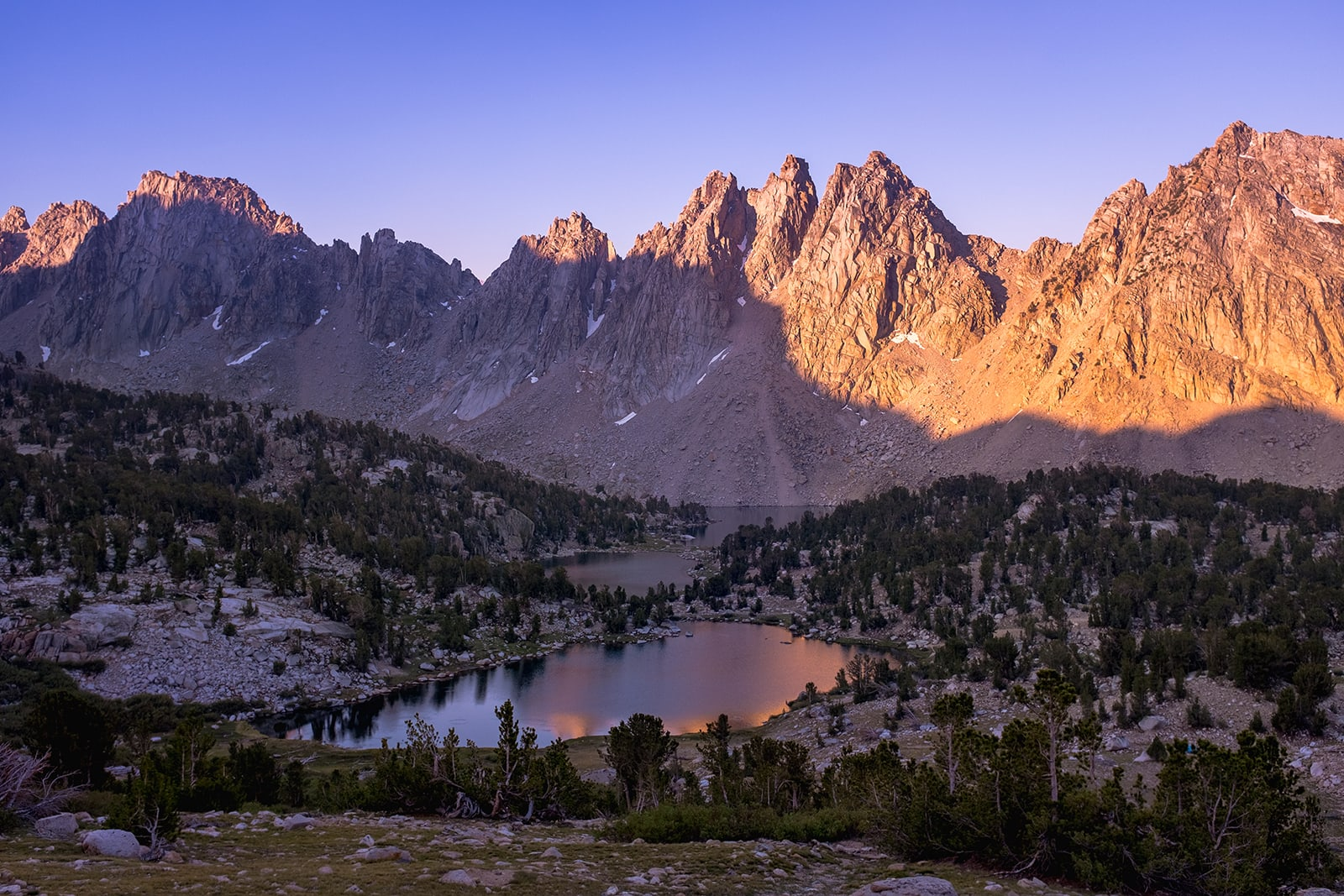 The sun crests the horizon to reveal the peaks near Kearsarge Pass.